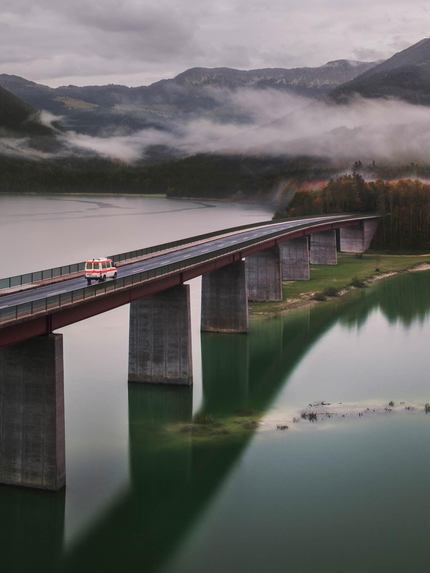 Werbefotografie eines DRK-Rettungswagens auf einer Brücke über einem See für die Imagekampagne des Jahreskalenders