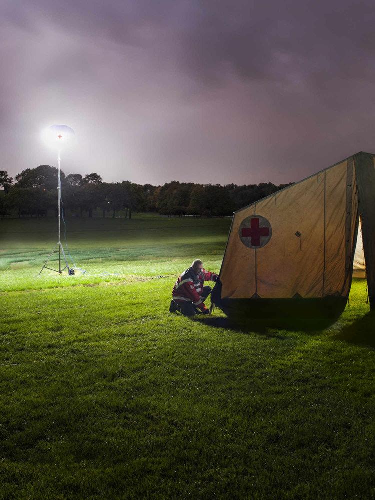 Werbefotografie für das DRK. Nachtaufnahme des Aufbaus eines Einsatzszelts auf freier Wiese für den Jahreskalender
