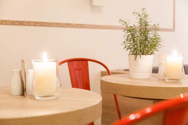 Tisch mit Stuhl, Kerze und Rosmarin bei dean&david