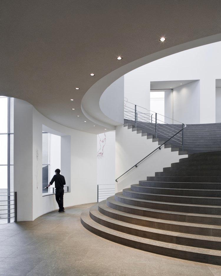 Architekturfoto des Kunstmuseums Bonn, ein Mensch steht am Fenster, eine Treppe führt nach oben, Innenaufnahme