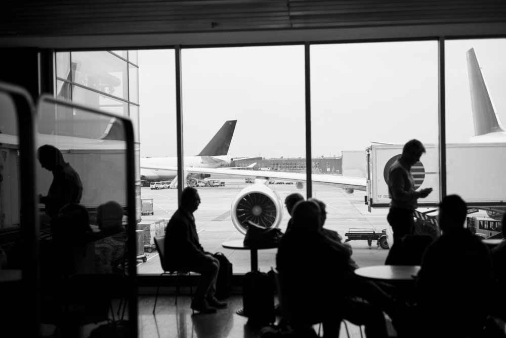 Menschen warten auf Flugzeug und Boarding in Lounge am Flughafen in Silhouette, schwarz-weiß, für SFS Aircraft Components