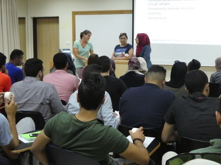 Professor Lisa, Dr. Summer, and a student translator stand before the very packed room of students.