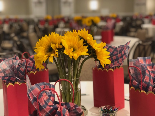 """Kelly Plosker worked her magic in the ballroom and carried the """"Fully Alive"""" theme with bursts of color as seen in these sunflowers and red goodie bags."""