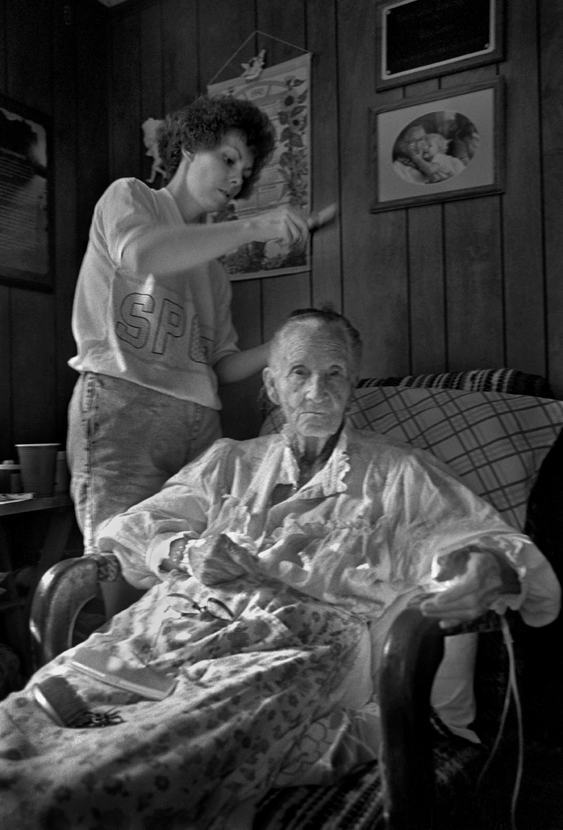 Debbie Chandler brushing her grandmother's, Dellie Norton, hair, Sodom, Madison County, North Carolina, 1991