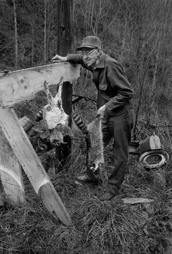 Paul Anderson skinning raccoons, Big Pine, 1978. From  Little Worlds
