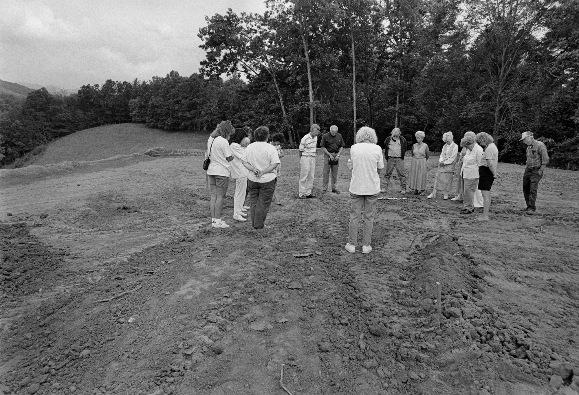 Family members praying over graves in the new Little Ivy Church Cemetery, Mars Hill, NC 1996. from  The New Road