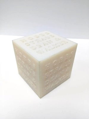 Branded cube 3D printed with glass-filled nylon using selective laser sintering (SLS).