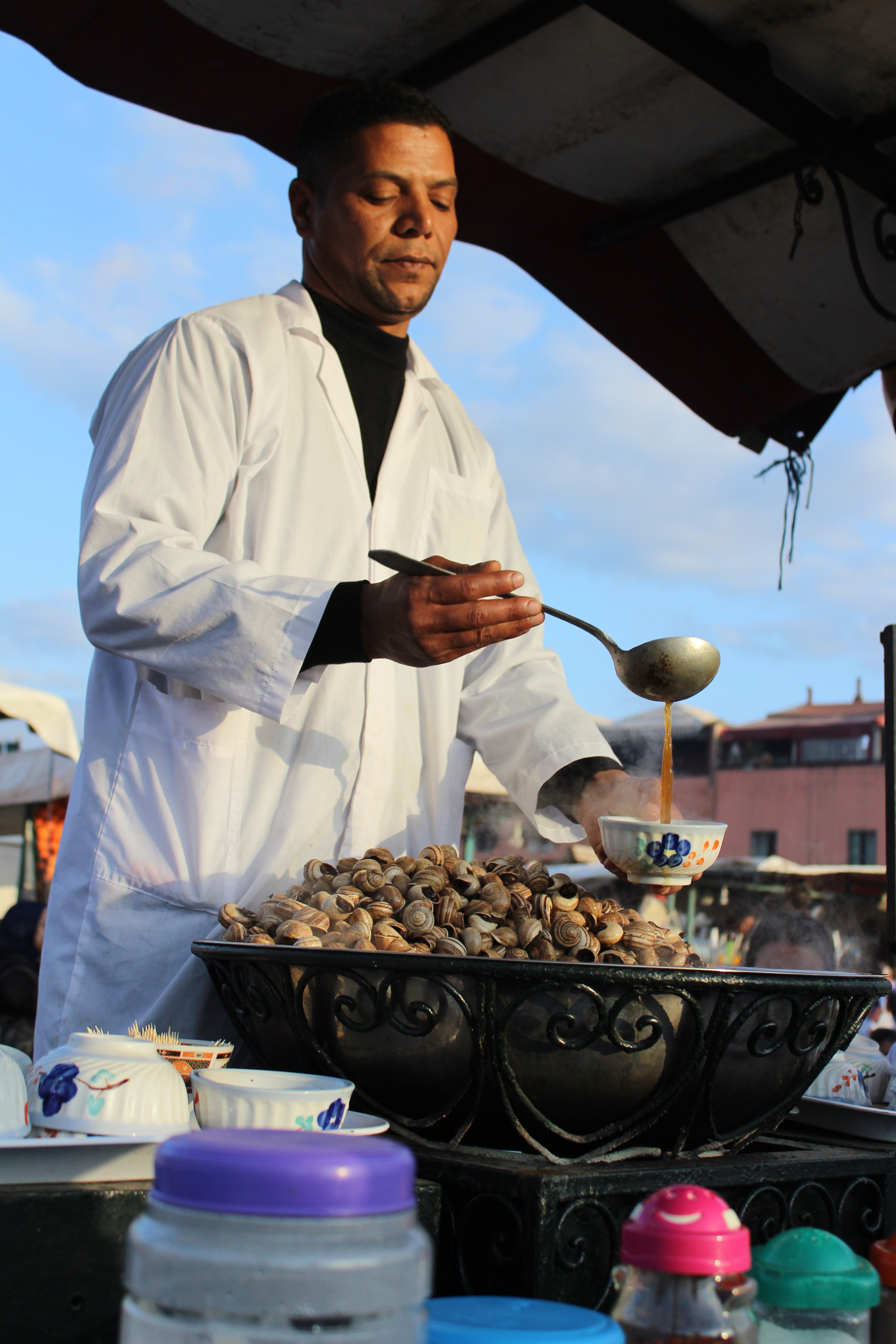 Snail stall owner in Marrakech preparing some cooked snails for a customer