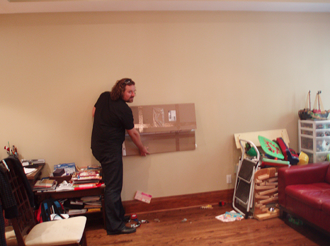 James Janz rearranging furniture in a client's home.