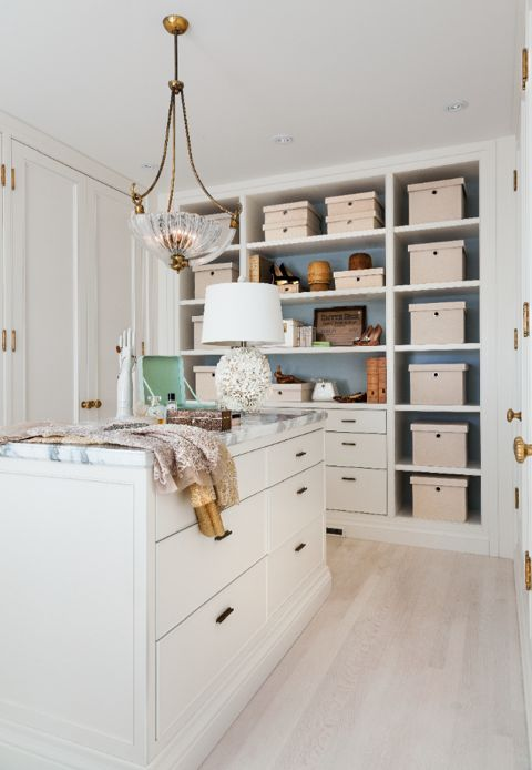 A clean contemporary makeup area featuring 1930's brass sconces and hardware that leads from the walk-in closet to the master suite's four-poster brass bed. (Casey Design/Planning Group Inc. - Photo by Donna Griffith)