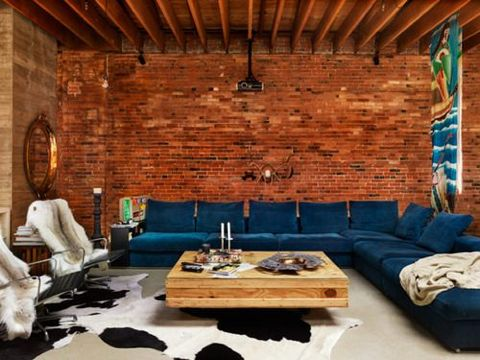 This indigo sofa contrasts wonderfully against the red brick backdrop - inviting and rustic.   (Veronica Love Archie ).