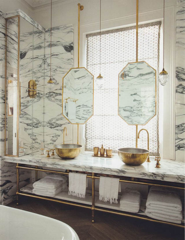 The combination of the Arabescato marble and the unlacquered brass provides plenty of glamour and drama in this master ensuite. ( Maddux Creative  - photograph by Ricardo Labougle)