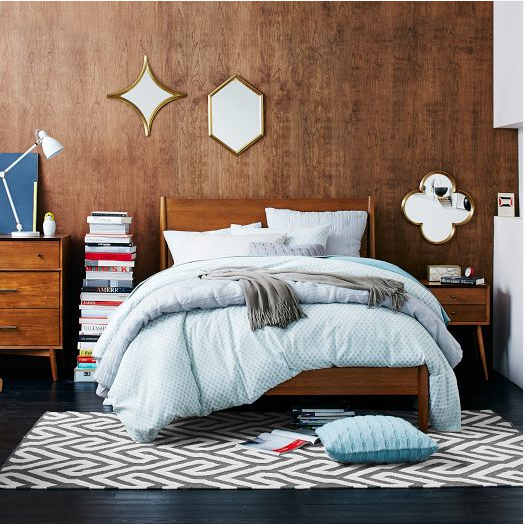 This simple wood stained bed frame in the med-century modern bedroom by West Elm is full of texture, pattern and colour. What a relaxing and intriguing haven to come home to after a long day! ( West Elm )