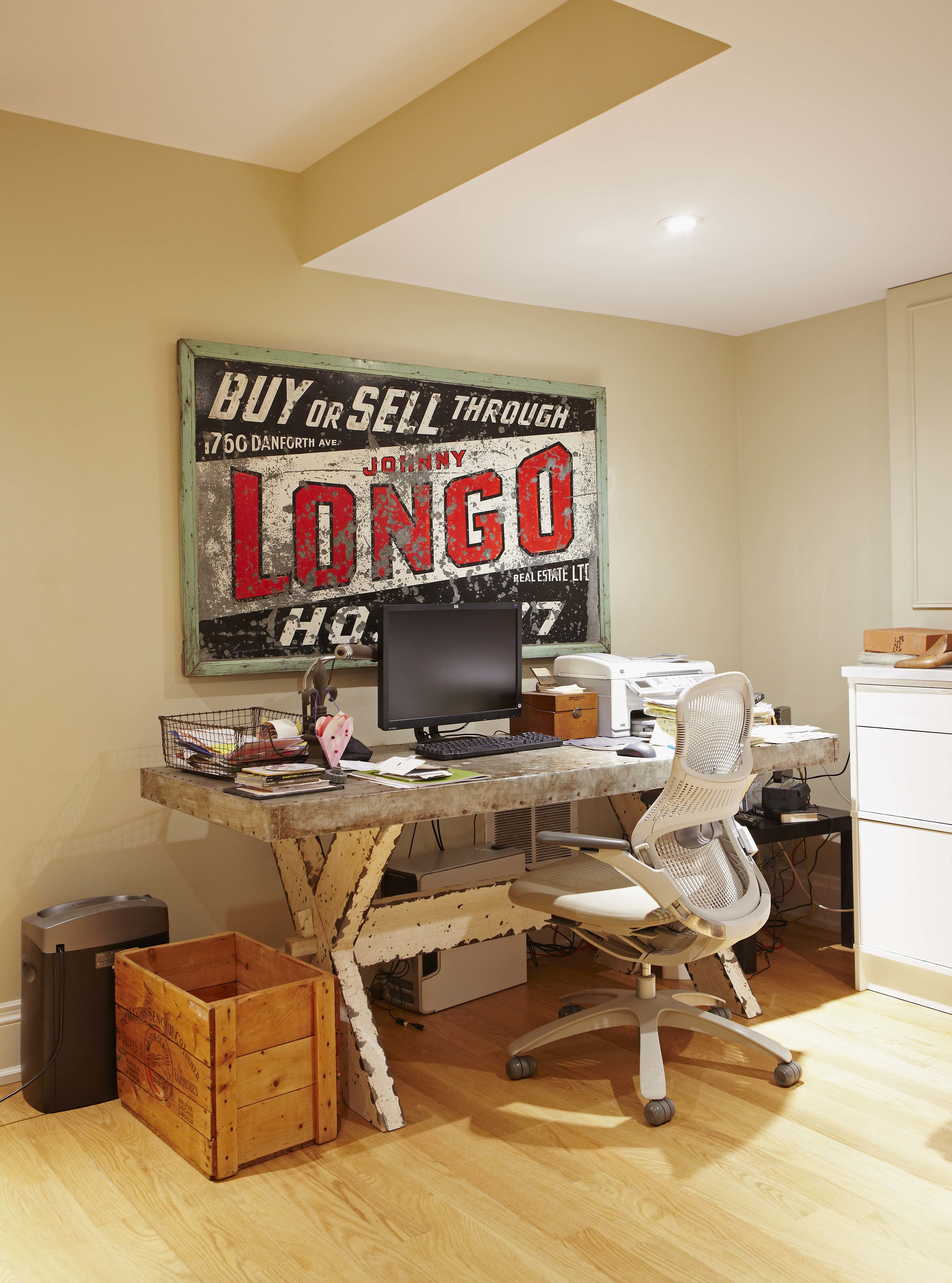 An antique industrial sign and desk provide character to this home office for our client and their family. (Casey Design / Planning Group Inc. - photograph by Michael Graydon)