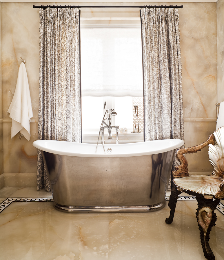 The Waterworks pewter tub and fixtures is the centrepiece of this bathroom. The pewter finish is a foil to set off the onyx walls and floors. One of my signature elements in my work is to add unexpected drama and warmth which here is achieved  with the full length silk curtains and the antique shell chair.   (Photography by Ted Yarwood)