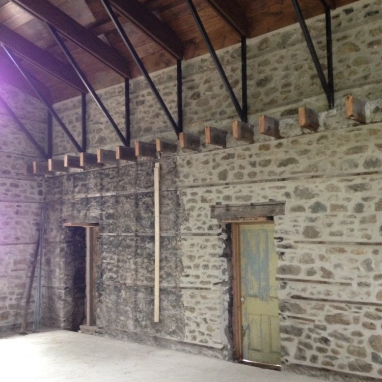 In process: the restored stone walls on the right and the damaged walls still on the left to be worked on. Also, see the cut off 2nd floor joist, new metal struts and new vaulted ceiling clad in warm stained wood. The joists were re-used throughout the project including in the kitchen ceiling. In the final solution here we installed hidden perimeter lighting inside of reclaimed wood valances.