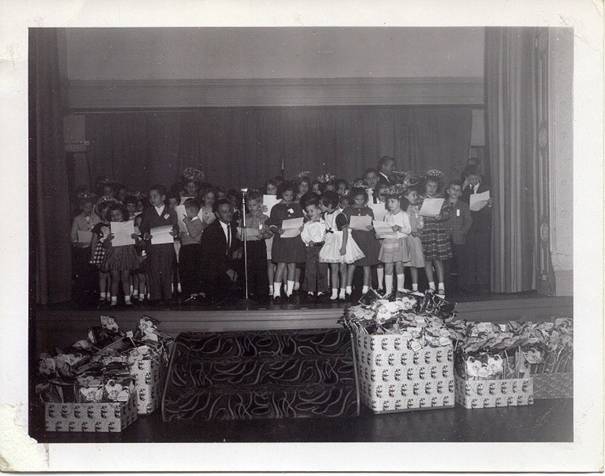 "Christmas party for the Cleveland Cap and Screw factory, where Howard's father worked, circa 1960, with little Howard at the microphone. Howard says e ach year a magician performed at the party : ""The magician was the entertainment draw for all the kids. He'd always bring up one kid from the audience and pull satin napkins out of their ears. When he asked for volunteers, I remember my heart always raced with the dread that I'd be picked, and the fear that I wouldn't."""