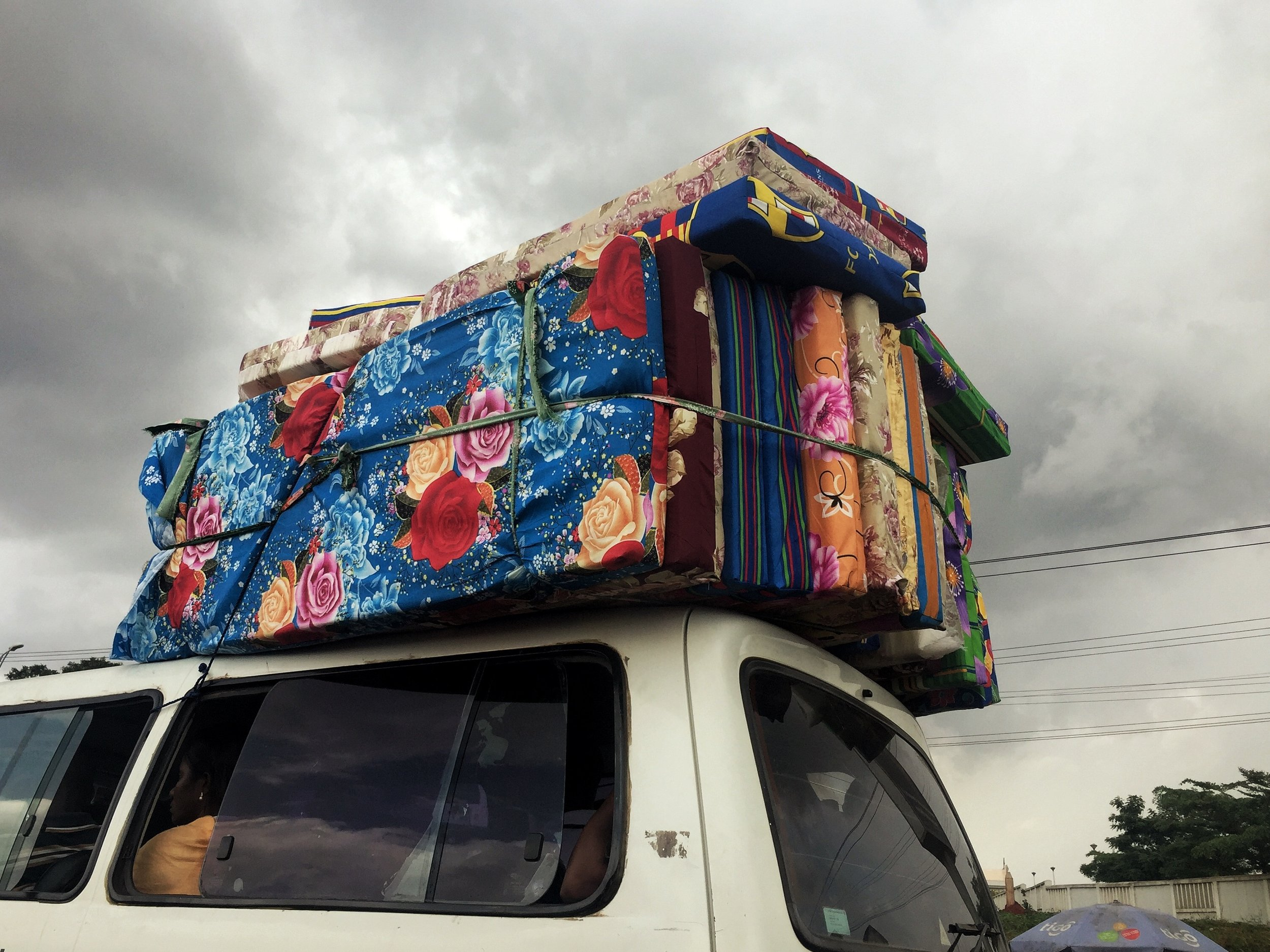 Children's mattresses tied to the top of a van during rush hour.