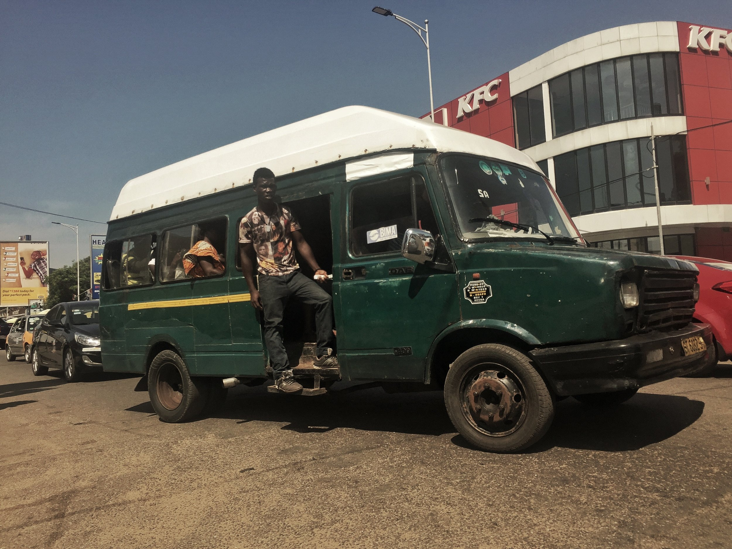 The mate of this trotro calls out destinations to passengers and collects fares.