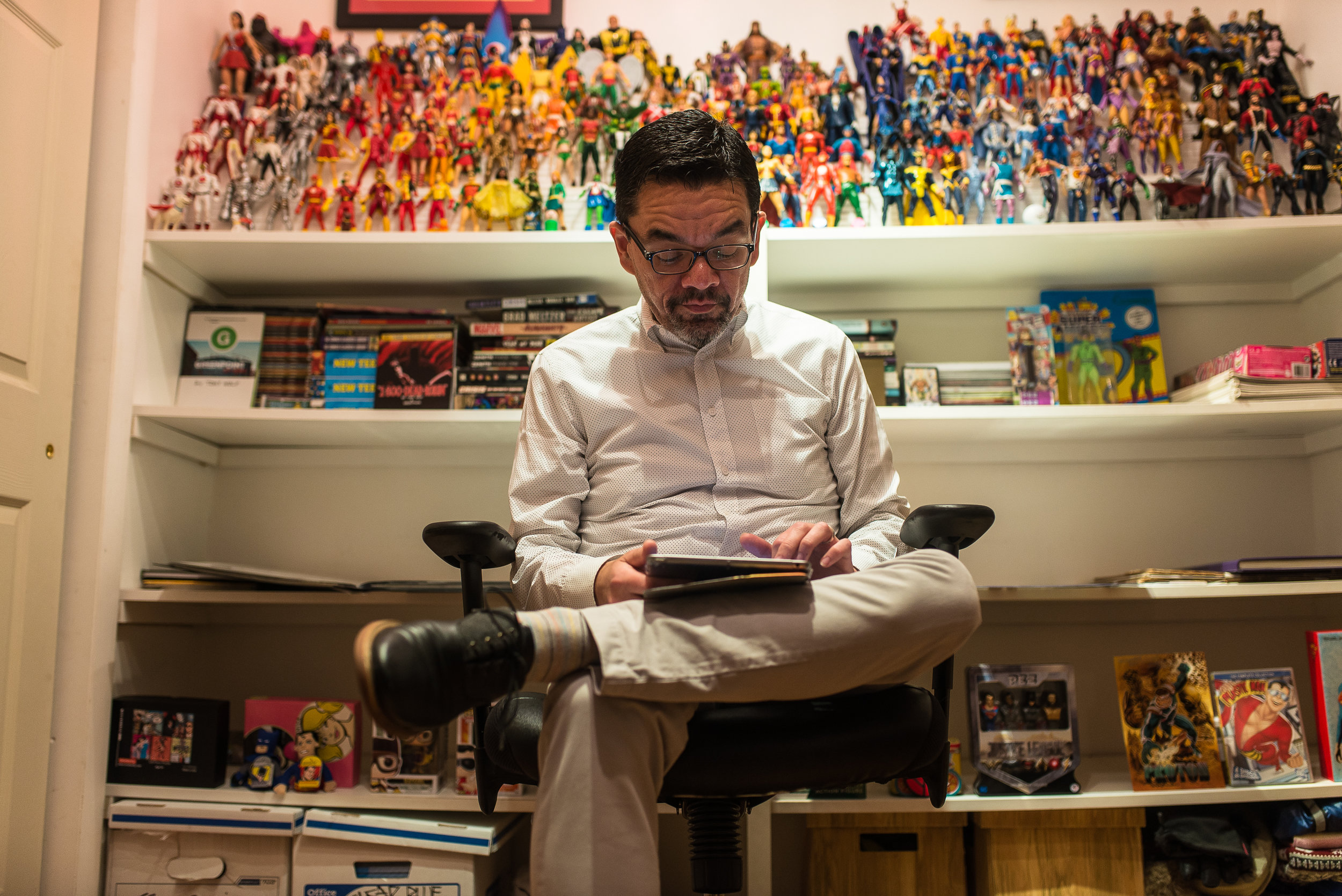 George Gustines reads the latest edition of comics on his tablet in his home office on the Upper West Side.