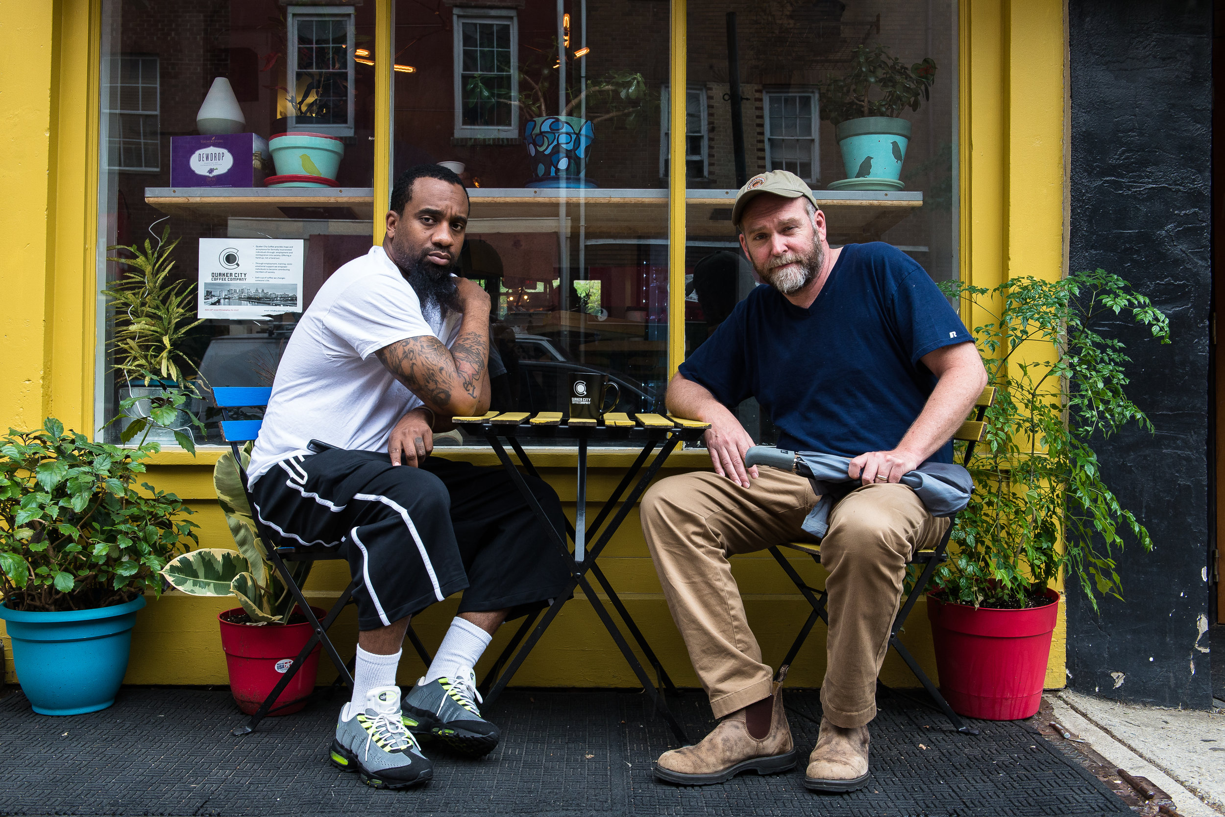Christian Dennis and Bob Logue, co-owners of Quaker City Coffee, sit outside their coffee shop in Philadelphia