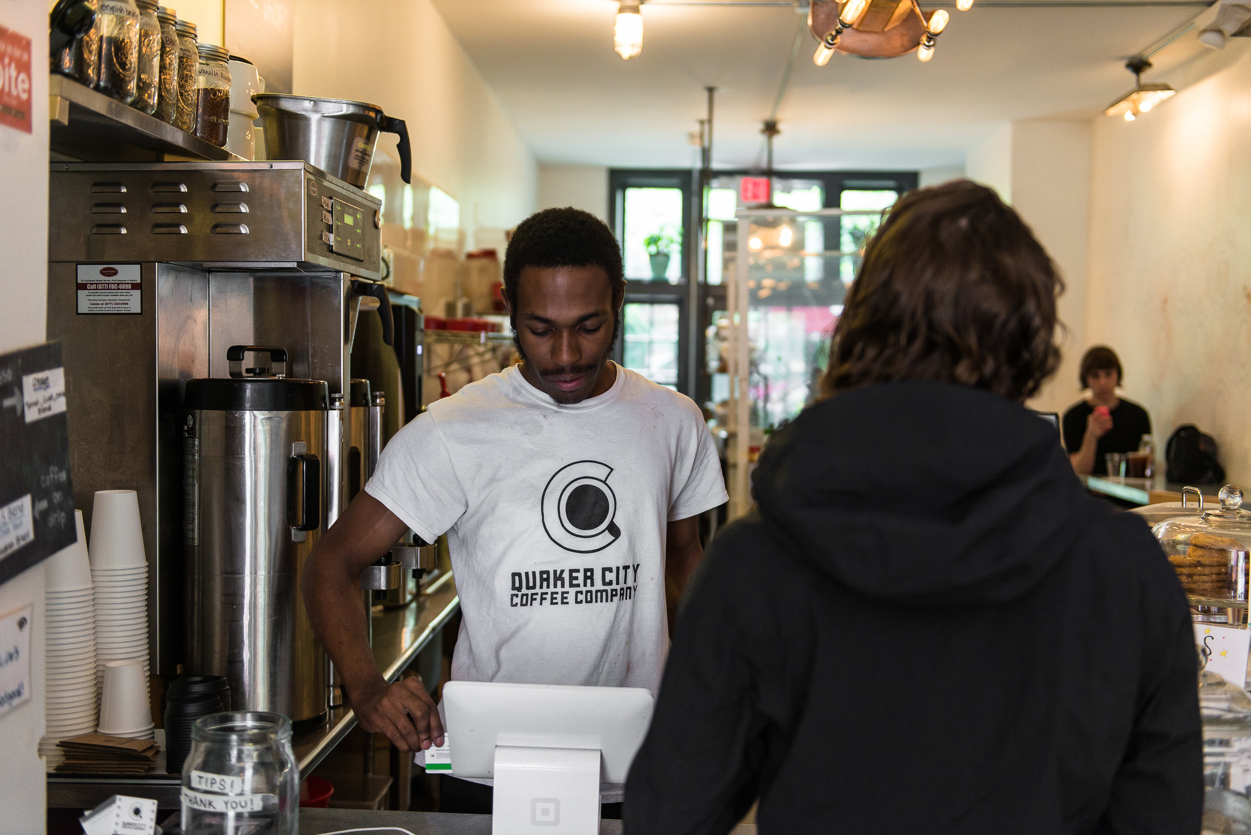 Jayson McCoy, a barista at Quaker City Coffee, tends to a customer.