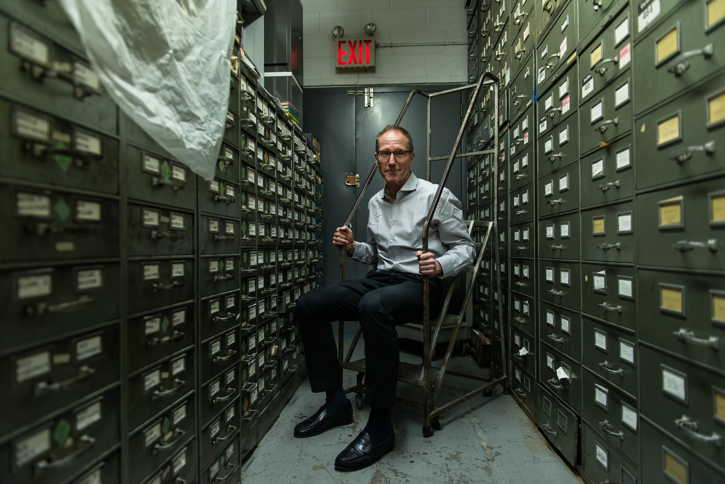 """Steve Lohr, NY Times journalist, sits for portrait inside """"The Morgue"""" — a storage facility for archival news."""