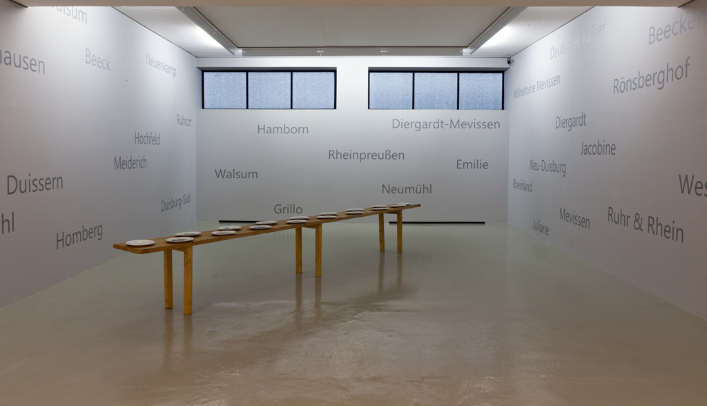 Exhibition: Kunst und Kohle  2018, Ruhrgebiet   Glück Auf I, 1991 ; miners portraits printed on porcelain plates, wooden table, grey wall paint with names and locations of all coal mines in Duisburg (2018); Museum DKM, Duisburg