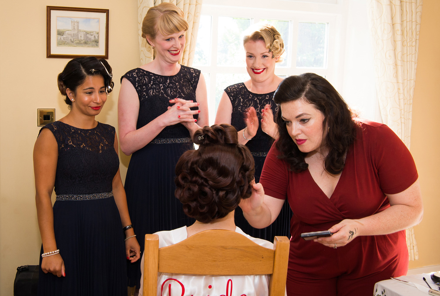 Photograph of bridal prep with bridesmaids watching