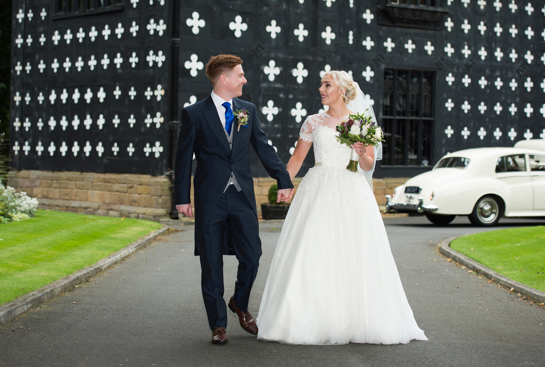 Bride and Groom walking along the drive at Samlesbury Hall
