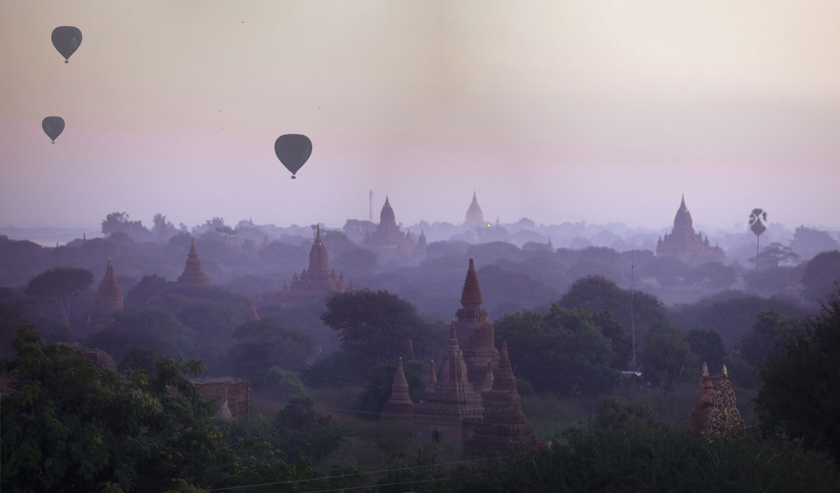Hot air balloons drift over the Bagan pagodas during sun rise.