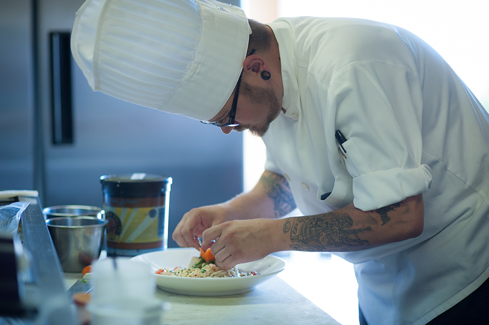 Chef Jonathan Nelson at Delicate Palate Bistro in Pacific City places the final touches.