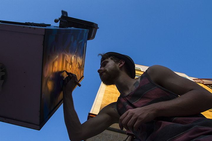 Street painter Alexander Southworth takes advantage of the last of the sunlight in Eugene Oregon to paint an electrical box on Pearl and 11th Streets.  Photo by   Sherrlyn Borkgren
