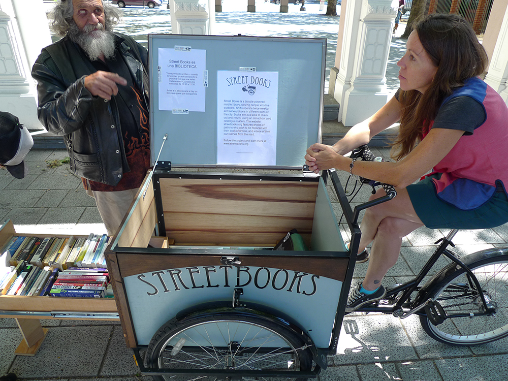 Laura Moulton talks to Woody during her shift at the Skidmore Fountain.  Street Books  is a bicycle-powered mobile library, serving people who live outside.  Photo by Melody Owen