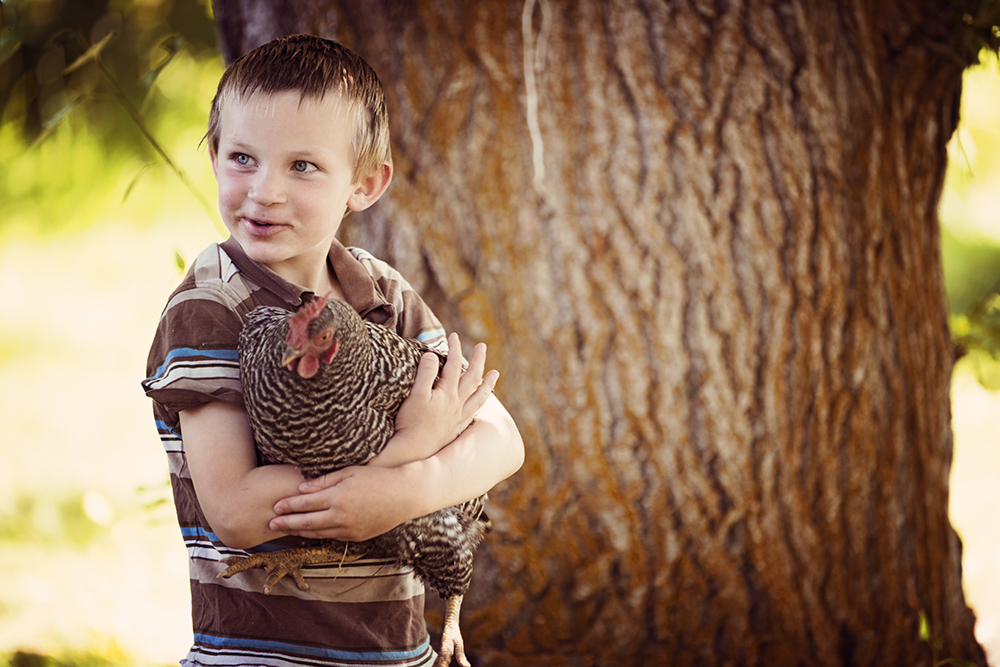 A member of the VanDoozer family clutches a chicken in Joseph.  Photo by Erika Plummer
