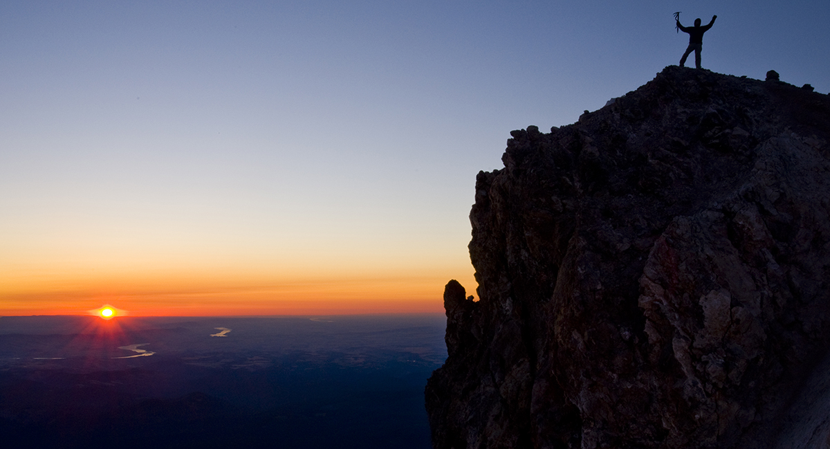 Dick Arnold celebrates sunrise from the top of Mt. Hood.  Photo by Peter Marbach