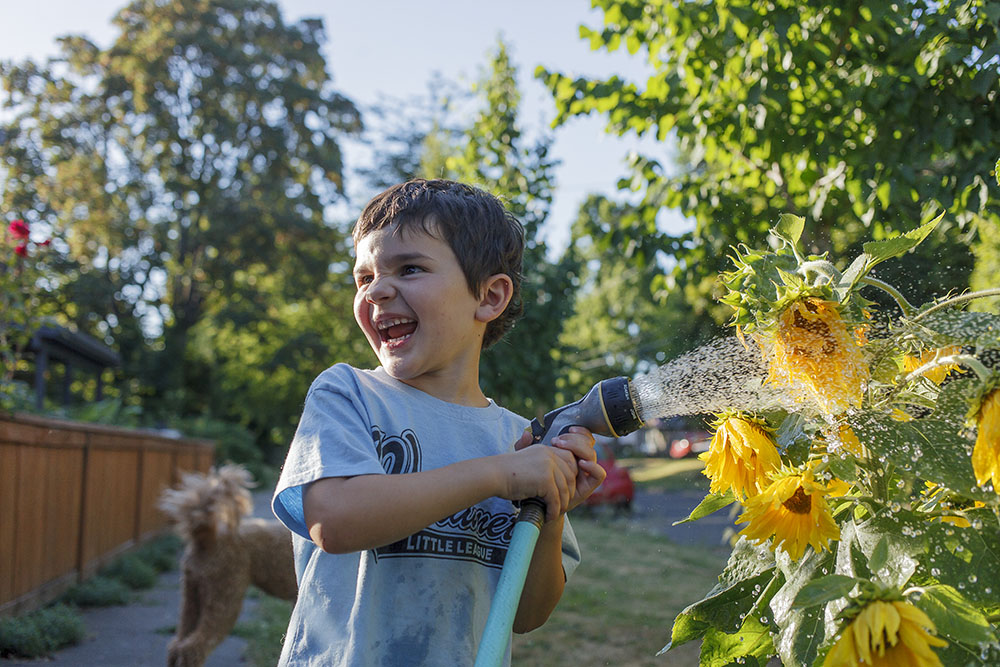 A young boy helps water the flowers.  Photo by Stu Mullenberg