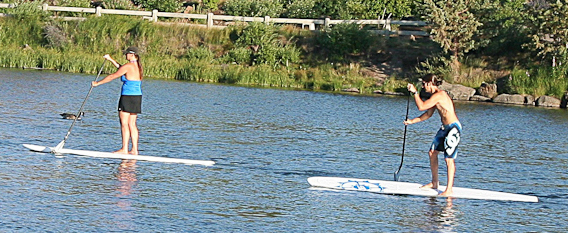 A couple paddle boarding on the Deschutes River in Bend.  Photo by Marji Parker