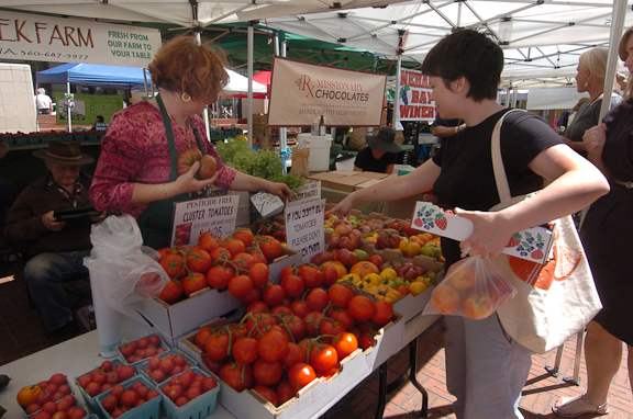 A shopper picks out tomatoes at a Farmer's market in Portland.  Photo by Mary Volm