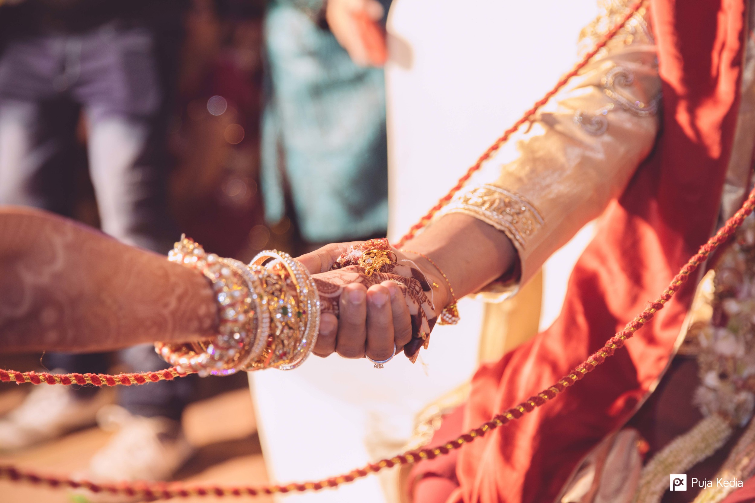 This knot and the joined hands of the couple symbolise the union of two souls joined together in holy matrimony.