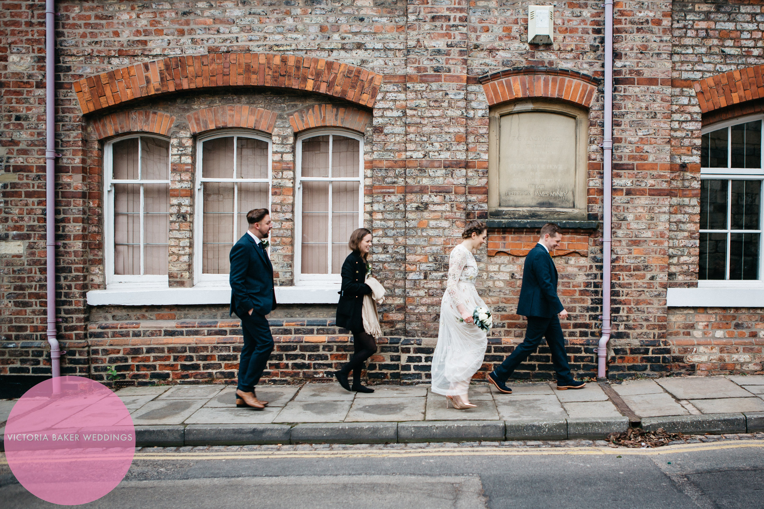 Bridal party walking - textured wall
