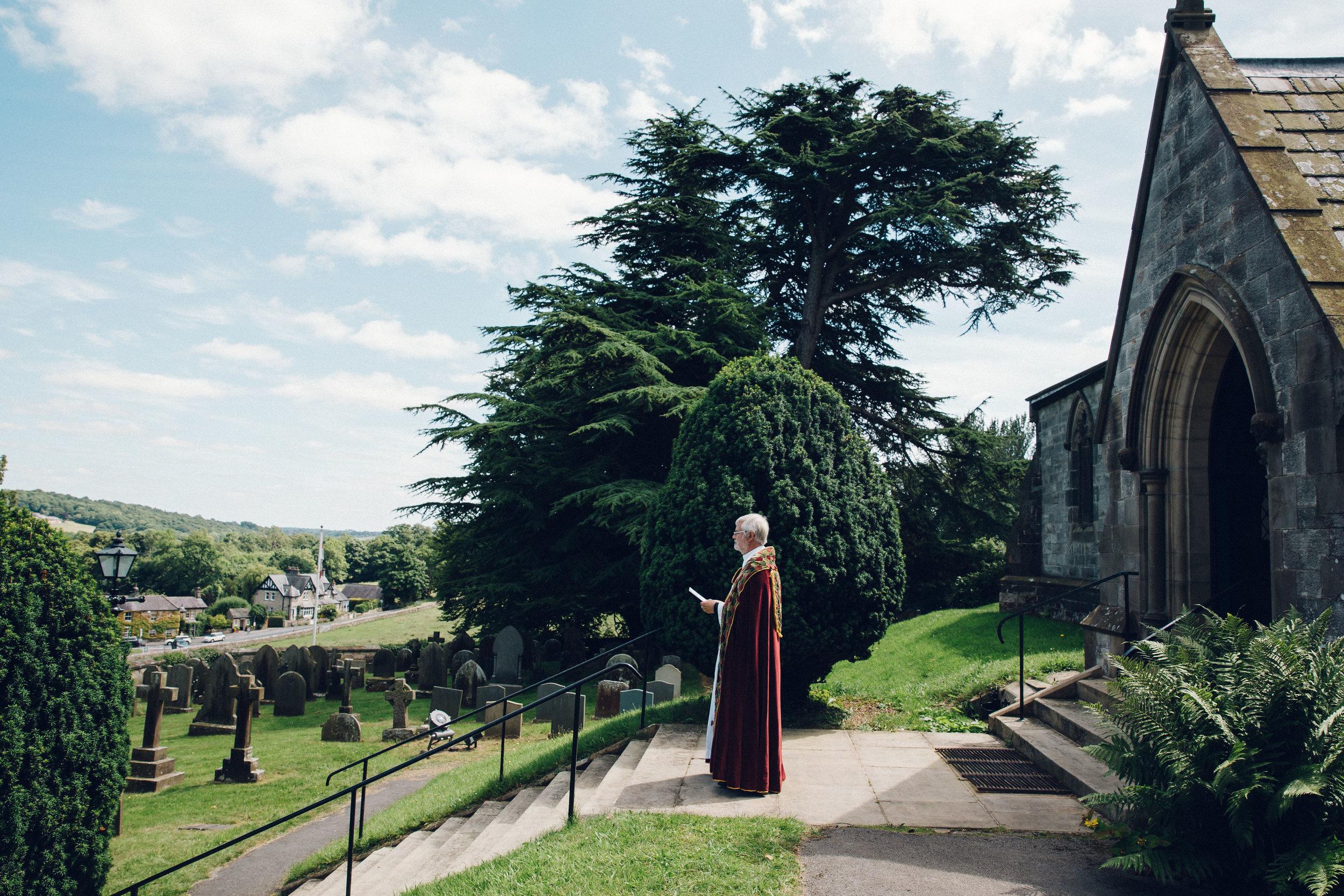 Vicar waiting outside church