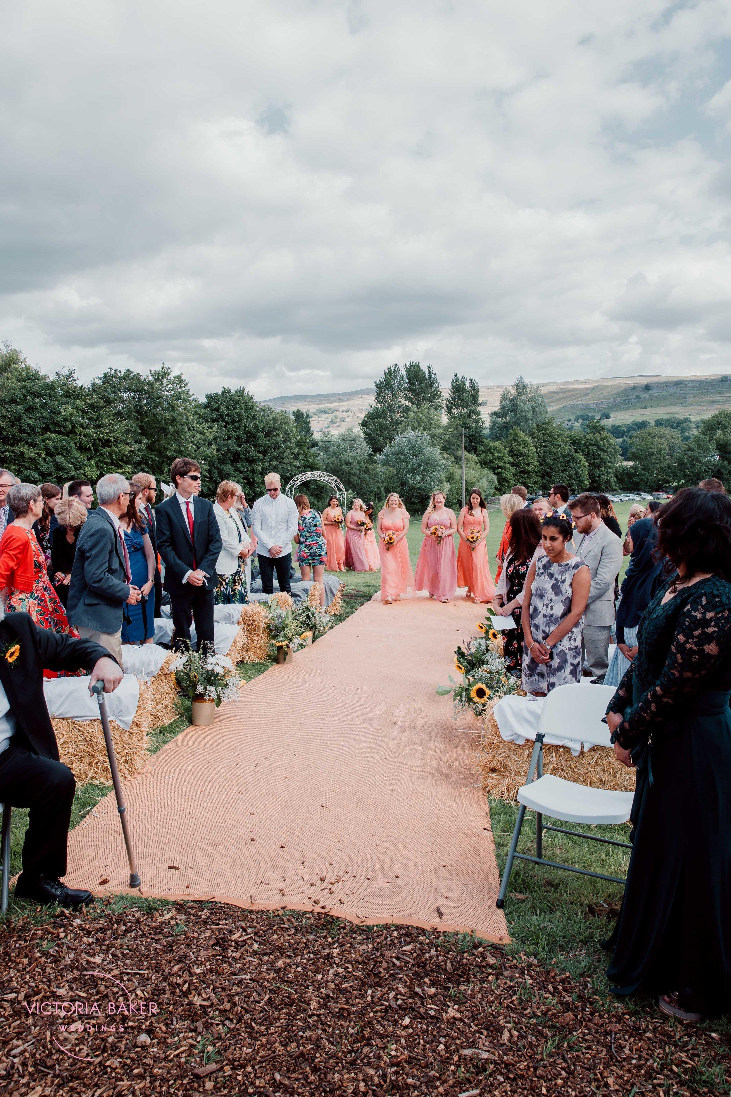Bridesmaids walking down the aisle at Kilnsey Park Estate Wedding Photography