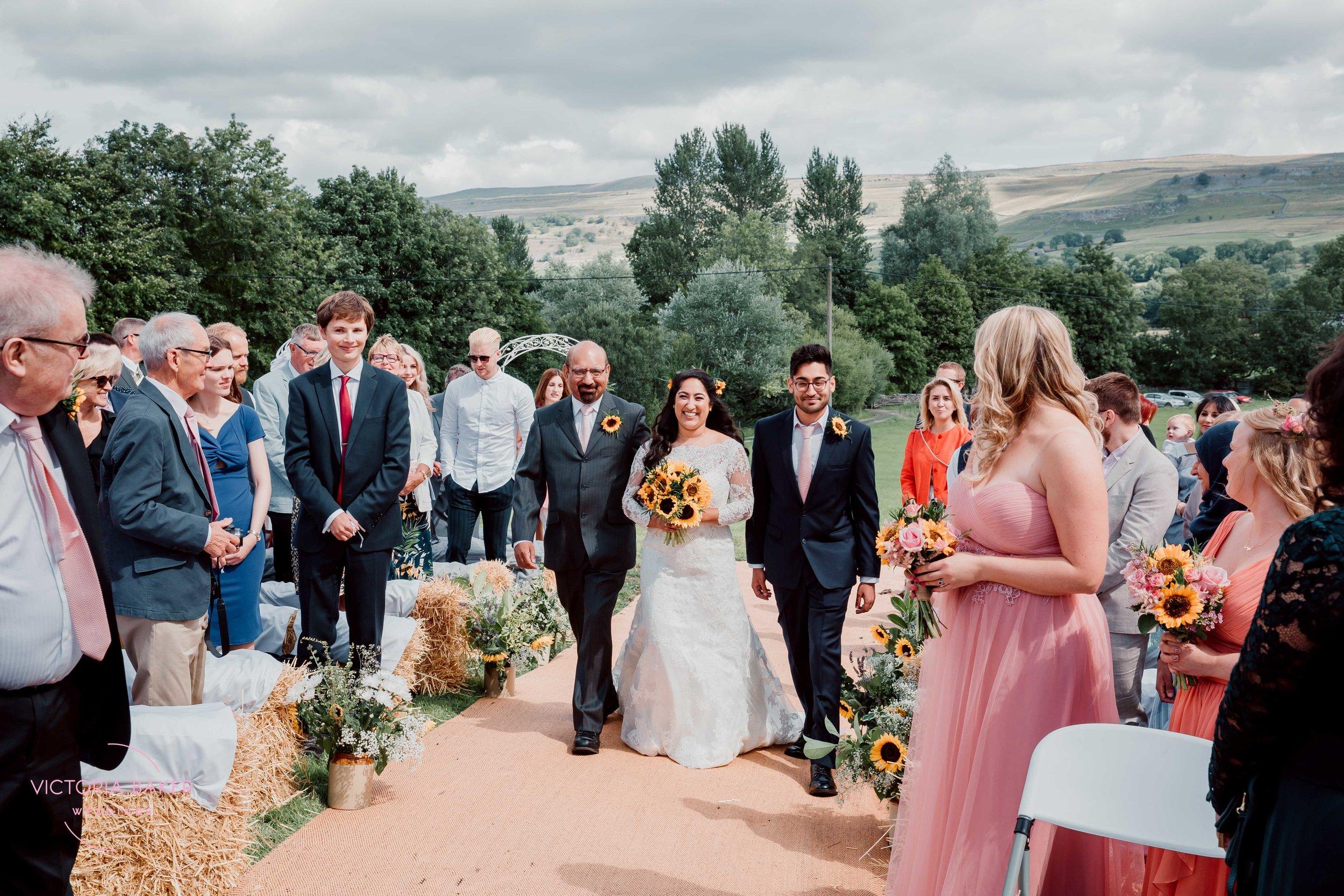 Bride walking down the aisle at Kilnsey Park Estate Wedding Photography