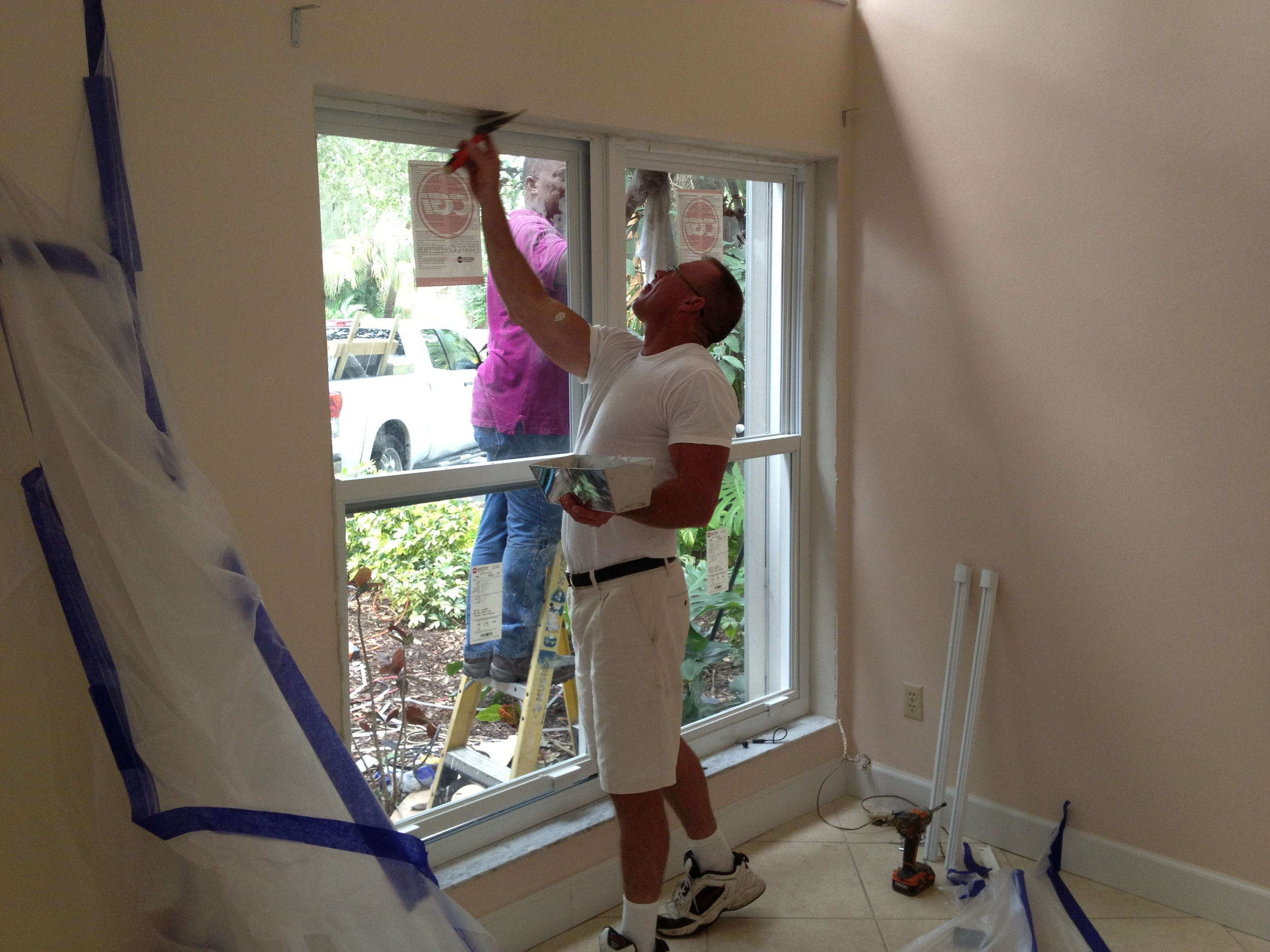 Paul Bourque patching the interior drywall after installing new windows.