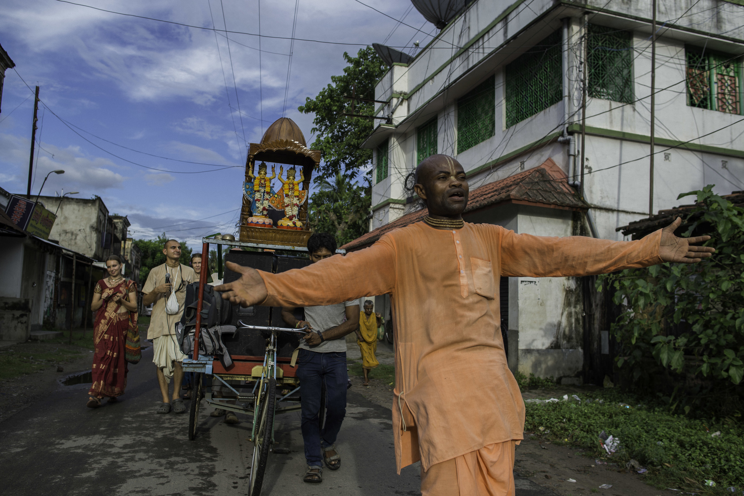 Devotee leading the Hare Nam through a village across the Ganga