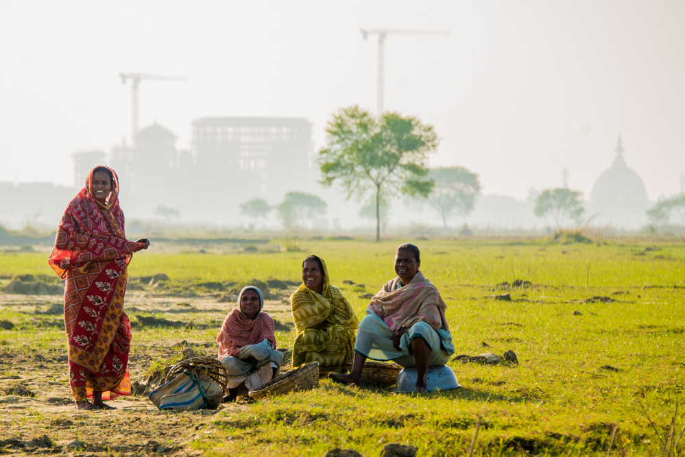 In the background, the new Temple of Vedic Planetarium dominates the Mayapur skyline, as the local women go to work on the fields