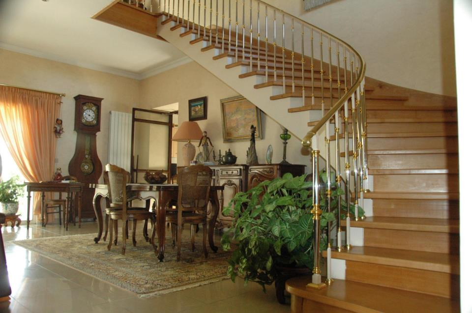 Curved traditional staircase with brass railing