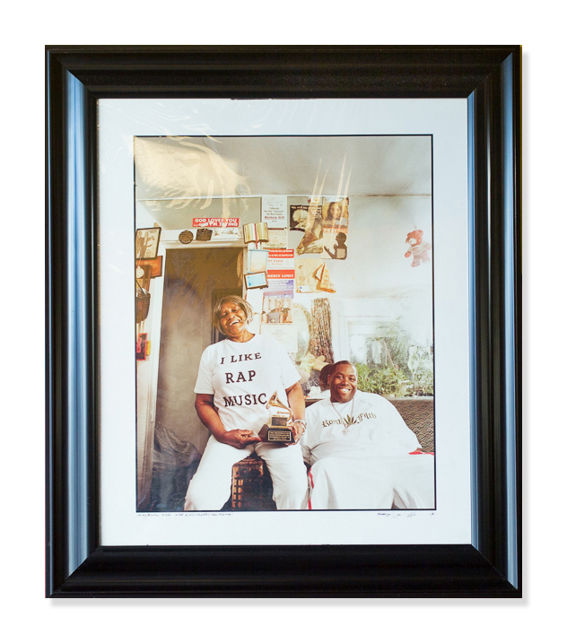 Killer Mike with his grandmother, the late Mrs. Bettie Clonts, holding his Grammy Award. This photo hangs on the wall of his barbershop.