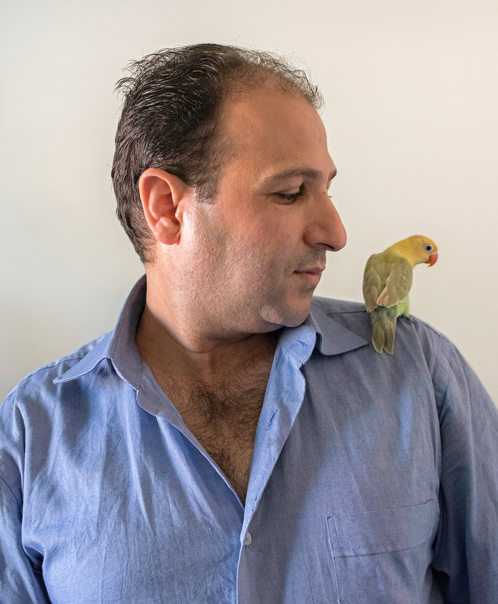 Hani Keddo with his Lovebird. Before he and his family were resettled in Clarkston, Hani owned his own shop in Syria that sold handbags and shoes. However, his shop was bombed, and he lost everything. Hani now drives a van pool, helping others in the Clarkston refugee community who need transportation.